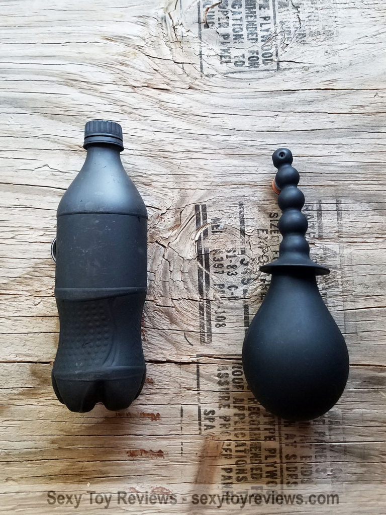 All silicone enema bulb pictured next to a standard US 20oz cola bottle