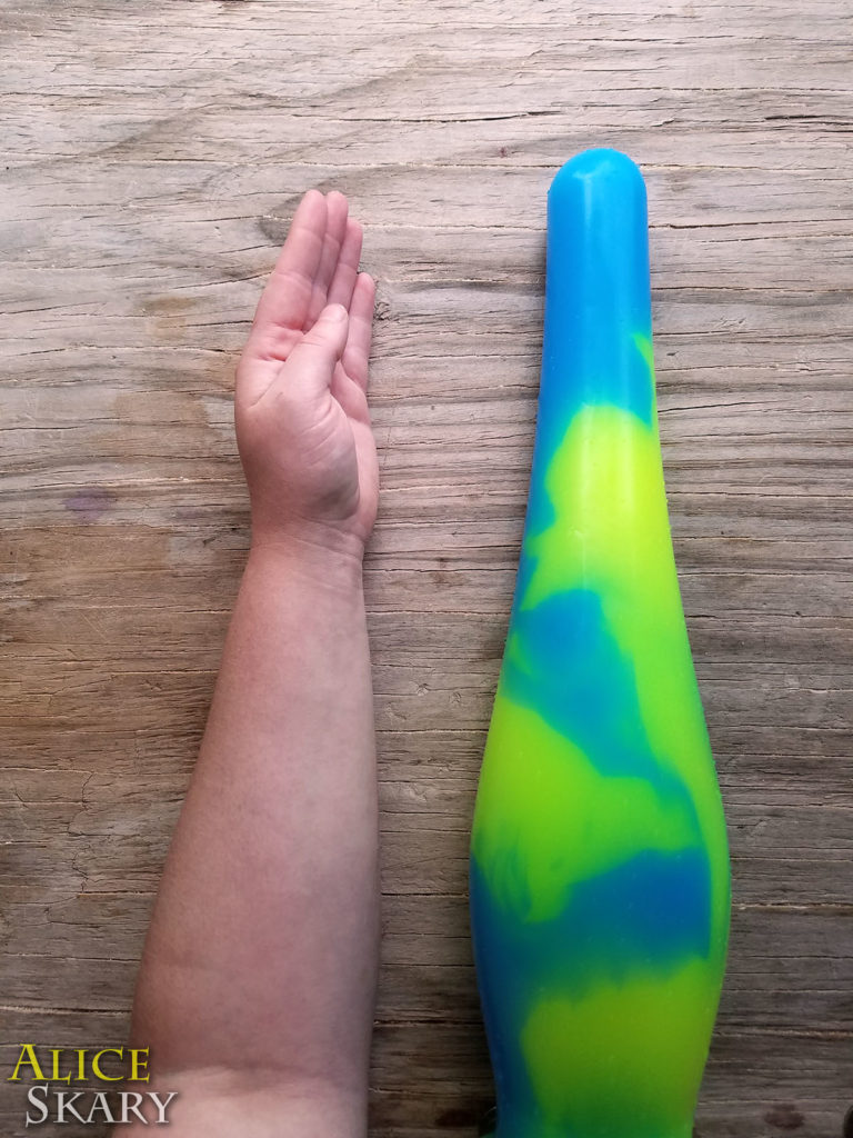 "The ""Intense"" silicone dildo is pictured next to a forearm"